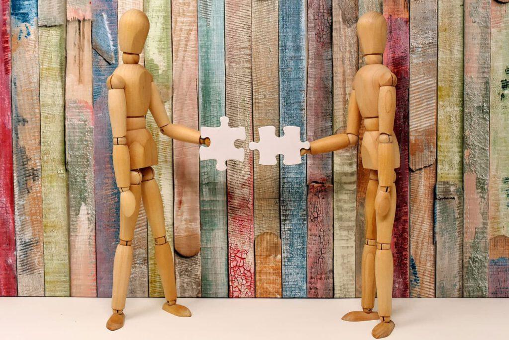 2 Figuren setzen ein Puzzle zusammen